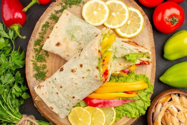 黒にレモンスライスと緑のスライスしたシャワルマ肉サンドイッチの上面図