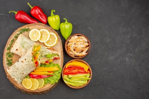 Вид сверху нарезанный шаурма вкусный мясной сэндвич с ломтиками лимона на черном
