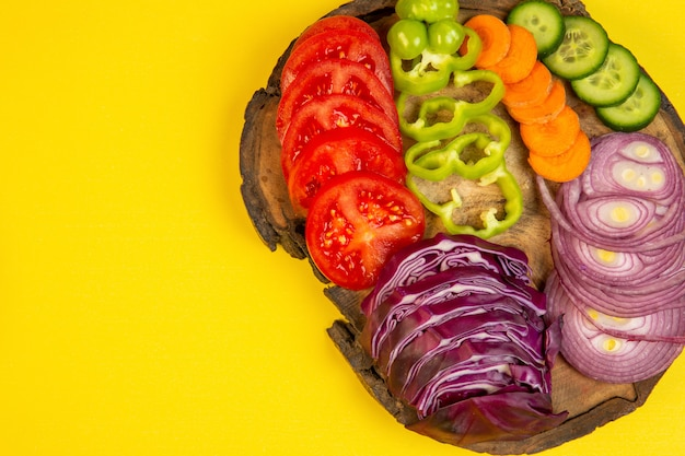 Вид сверху нарезанные овощи красная капуста лук помидоры сладкий перец морковь и огурцы на деревянной доске на желтый j