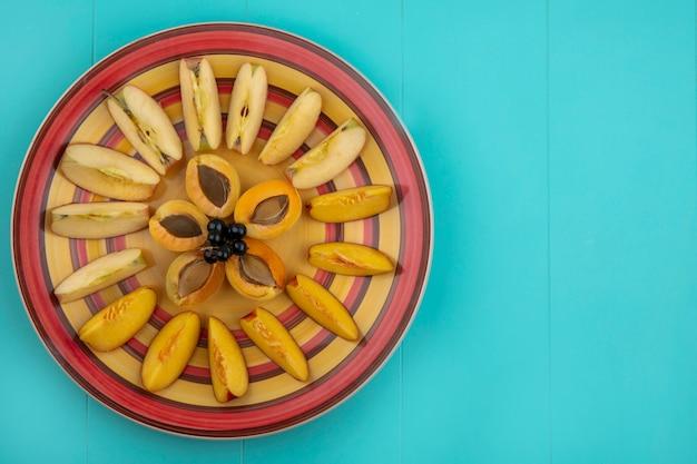 青い表面の皿にリンゴと桃とアプリコットのスライスのトップビュー