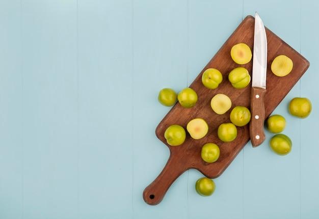 コピースペースと青色の背景にナイフで木製キッチンボード上の緑のチェリープラムのスライスのトップビュー