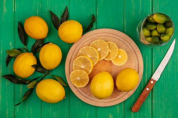 녹색 나무 벽에 고립 된 레몬과 함께 유리에 kinkans와 칼으로 나무 부엌 보드에 레몬 조각의 상위 뷰