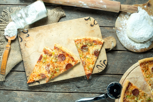Вид сверху ломтики пиццы салями с томатным соусом, зеленым перцем чили и специями