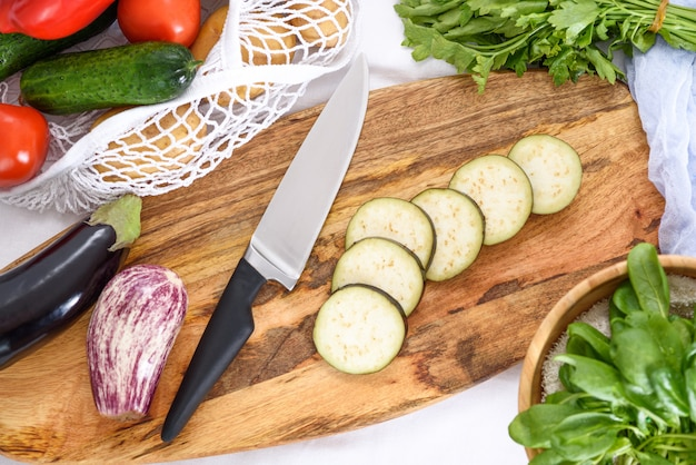 Вид сверху на нарезку овощей баклажан, перец, шпинат, салат, процесс приготовления домашнего ужина
