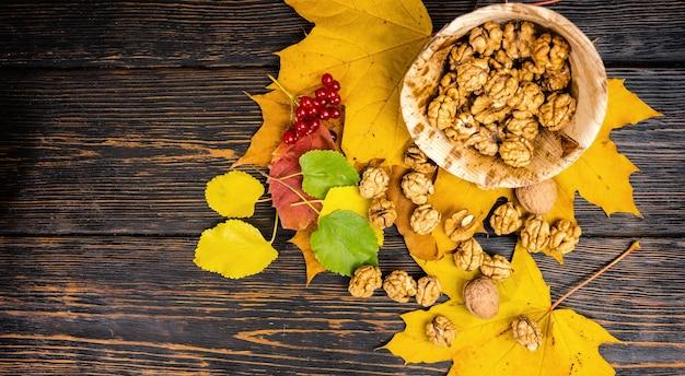 Вид сверху слегка разбросанных грецких орехов, лежащих на листьях возле деревянной тарелки с грецкими орехами на деревянном столе.