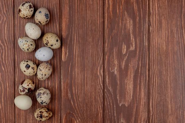 Вид сверху небольших свежих перепелиных яиц, изолированных на деревянном фоне с копией пространства