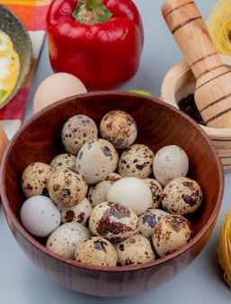 白地に赤ピーマンと木製のボウルに小さなウズラの卵のトップビュー