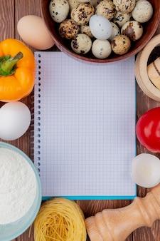 Вид сверху небольших перепелиных яиц на деревянной миске с белыми куриными яйцами с желтым перцем с помидорами на деревянном фоне с копией пространства