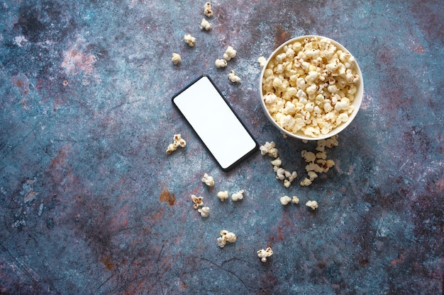 Вид сверху смартфона и попкорна на столе.