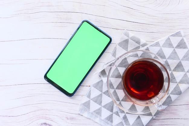 Вид сверху смартфона и чая на столе