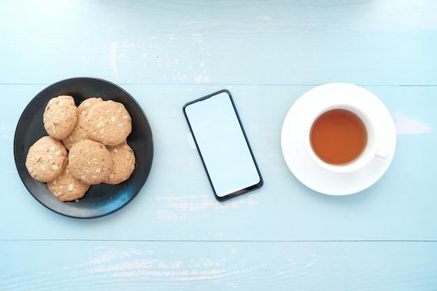 Вид сверху на смартфон печенье и чай на столе Premium Фотографии