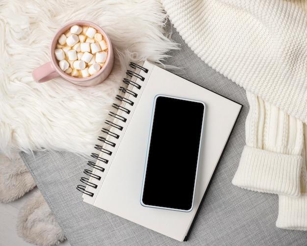 ホットココアのカップとスマートフォンとノートブックの上面図