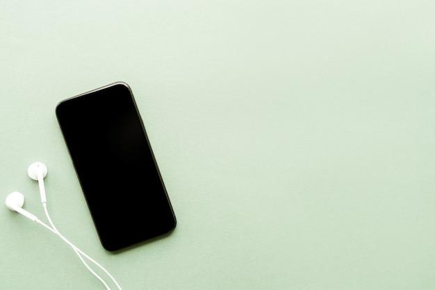 緑の背景に空白の画面のヘッドフォンとスマートフォンの上面図