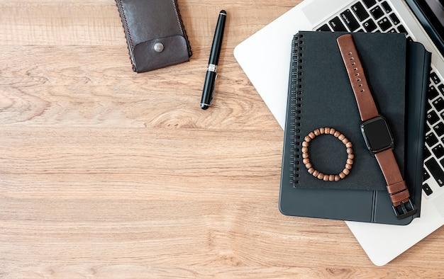자연 나무 테이블에 smartwatch, 구슬 팔찌, 노트북 및 노트북 컴퓨터의 상위 뷰