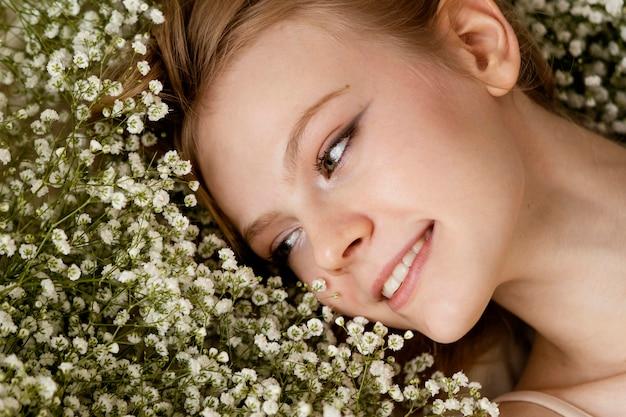 봄 꽃과 함께 포즈 웃는 여자의 상위 뷰 프리미엄 사진