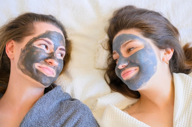 自宅でフェイスマスクとスマイリー女性のトップビュー