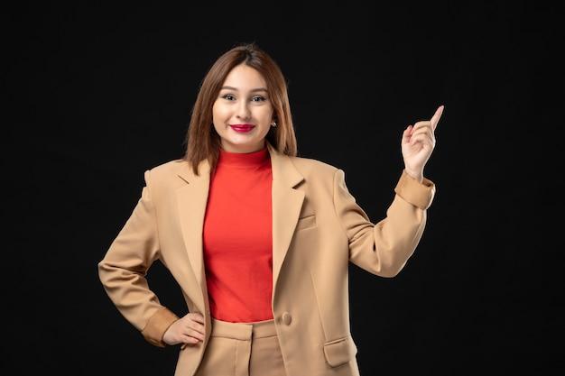 暗い上向きの明るい茶色のスーツを着て笑顔と自信を持って若い女性の上面図