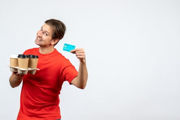 白い壁に注文銀行カードを保持している赤いブラウスの笑顔と幸せな若い男の上面図