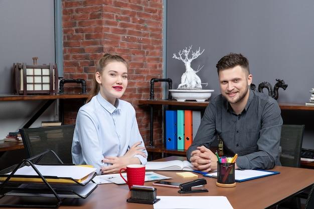 사무실에서 카메라를 위해 포즈를 취하는 테이블에 앉아 웃고 있는 동기 부여된 사무실 팀의 상위 뷰