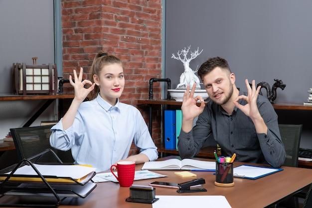 Вид сверху улыбающихся и мотивированных квалифицированных рабочих, делающих жест в очках в офисе