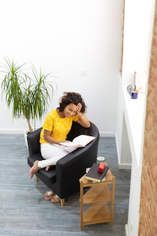 家で本を読んで笑顔のブルネットの女性の上面図。テキスト用のスペース。