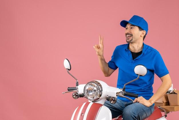 Вид сверху улыбающегося курьера в шляпе, сидящего на скутере, доставляющего заказы, делая жест победы на пастельном персике
