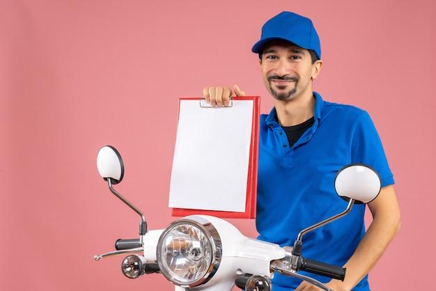 Вид сверху улыбающегося курьера в шляпе, сидящего на скутере с документом на пастельных персиках