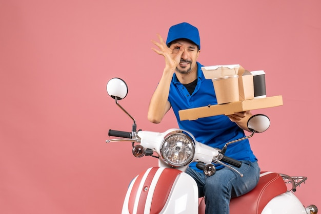 Вид сверху улыбающегося курьера в шляпе, сидящего на скутере, делая жест очки на пастельном персике
