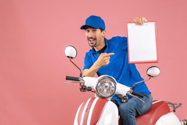 Вид сверху улыбающегося курьера в шляпе, сидящего на скутере, показывающего документ на пастельных персиках