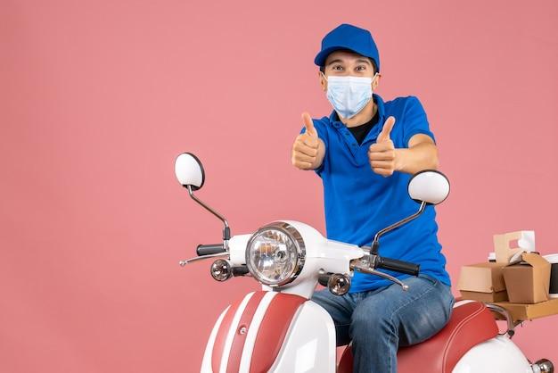 Вид сверху улыбающегося курьера в медицинской маске в шляпе, сидящего на скутере и делающего жест на пастельных персиках