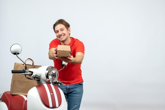 白い背景の上の注文を与えるスクーターの近くに立っている赤い制服を着た笑顔の配達人の上面図