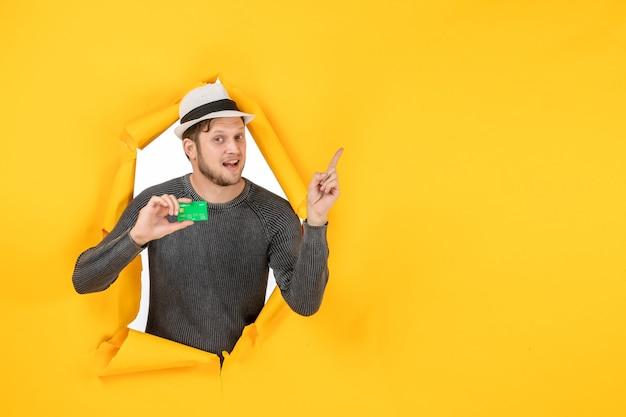 은행 카드를 들고 노란색 벽에 찢어진 가리키는 웃는 남자의 상위 뷰