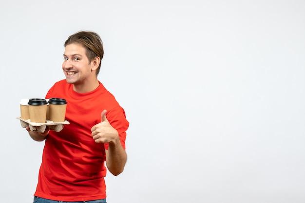 注文を保持し、白い壁に大丈夫ジェスチャーをする赤いブラウスで笑顔の幸せな若い男の上面図