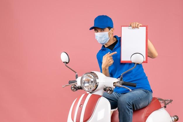 Вид сверху улыбающегося курьера в маске в шляпе, сидящего на скутере, показывающего документ на пастельном персике