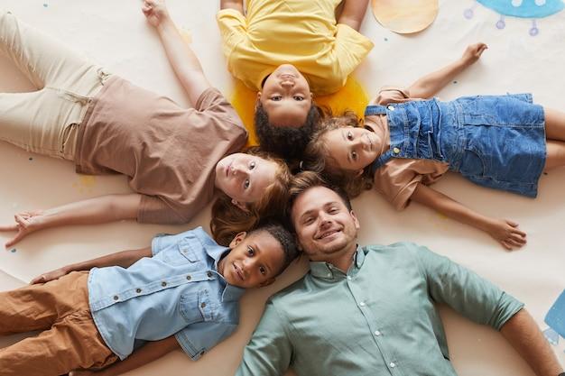 Вид сверху улыбающегося учителя-мужчины с многоэтнической группой детей, лежащих в кругу, развлекаясь в дошкольном учреждении или центре развития.