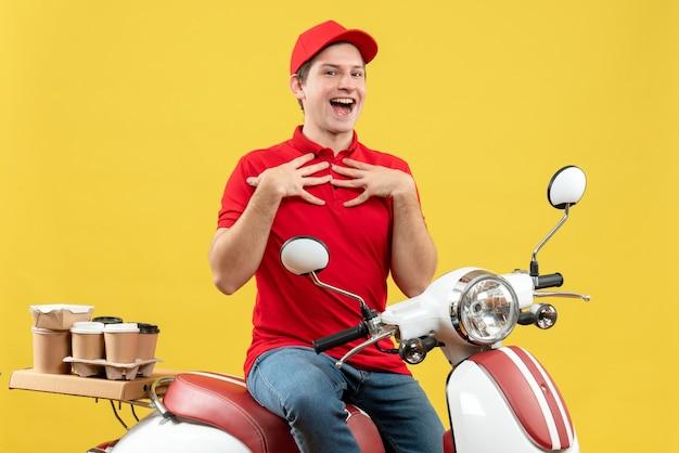 黄色の壁に自分自身を指しているスクーターに座って注文を配信赤いブラウスと帽子を身に着けている不確かな若い大人の笑顔の上面図