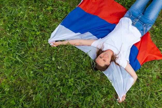 Вид сверху улыбающейся женщины лежит на национальном флаге россии на открытом воздухе