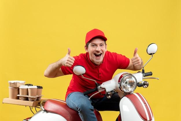 赤いブラウスと帽子をかぶって笑顔の若い大人の平面図は、黄色の壁に大丈夫ジェスチャーを作るスクーターに座って注文を配信します
