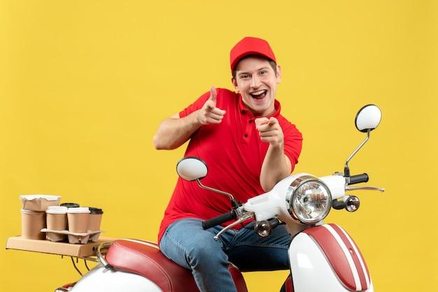 赤いブラウスと帽子を身に着けている笑顔の若い大人の平面図は、黄色の壁を前に向けてスクーターに座って注文を配信します。