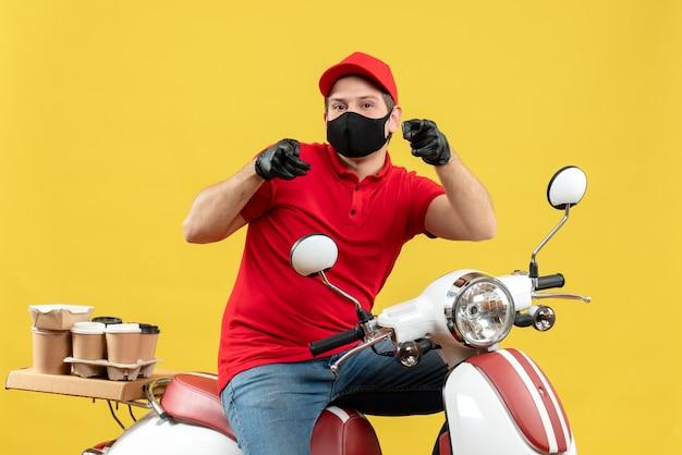黄色の壁を前に向けてスクーターに座って注文を配信医療マスクで赤いブラウスと帽子の手袋を身に着けている笑顔の若い大人の上面図