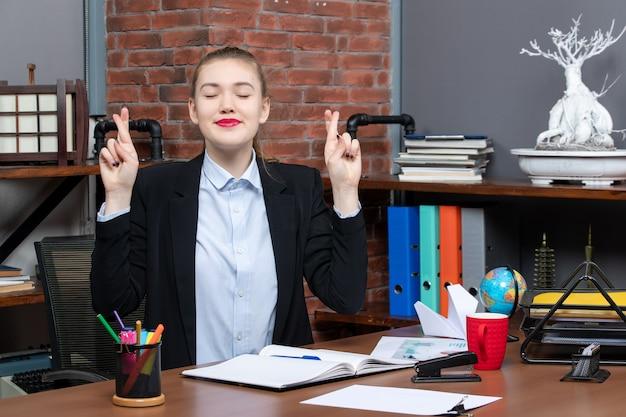 テーブルに座って、オフィスで何かを夢見て彼女の指を交差させてドキュメントを保持している笑顔の若い女性の上面図
