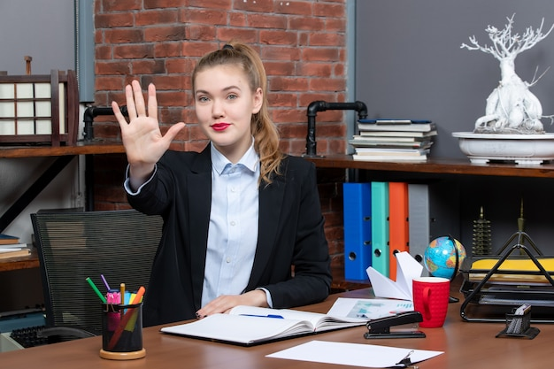 테이블에 앉아 사무실에서 다섯을 보여주는 웃는 젊은 여성의 상위 뷰