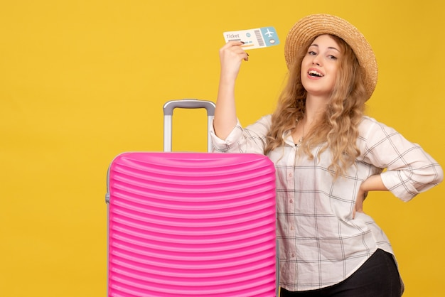 チケットを保持し、彼女のピンクのバッグの近くに立っている帽子をかぶって笑顔の若い女性の上面図