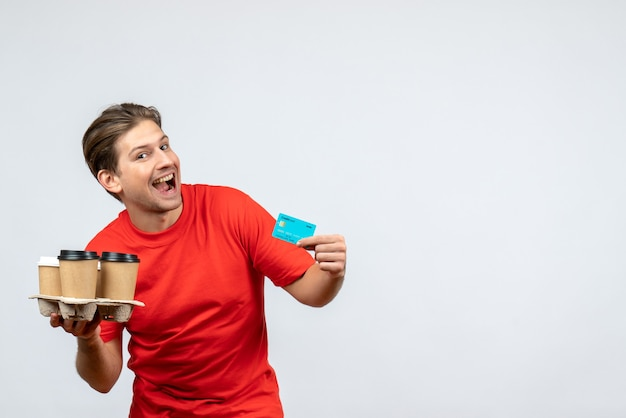 白い壁に注文銀行カードを保持している赤いブラウスで笑顔の若い男の上面図