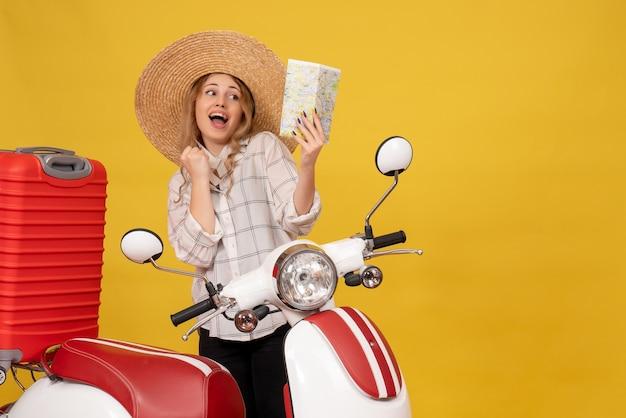 オートバイに座って地図を保持している彼女の荷物を収集する帽子をかぶって笑顔の若い女性の上面図