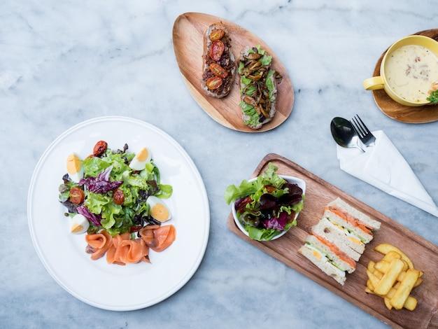 スープ、クラブサンドイッチ、テーブル上のスモークサーモンサラダの上面図。