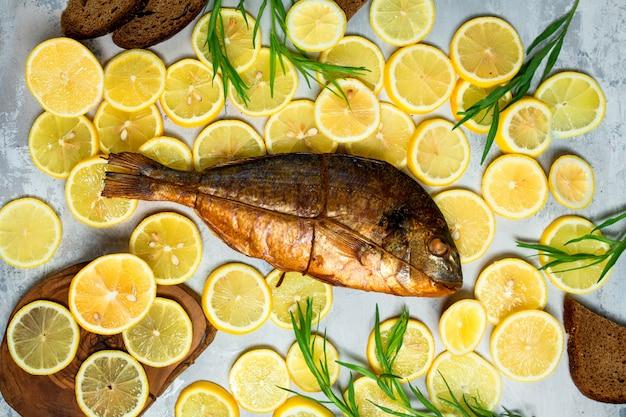 Вид сверху копченой рыбы в окружении ломтиков лимона