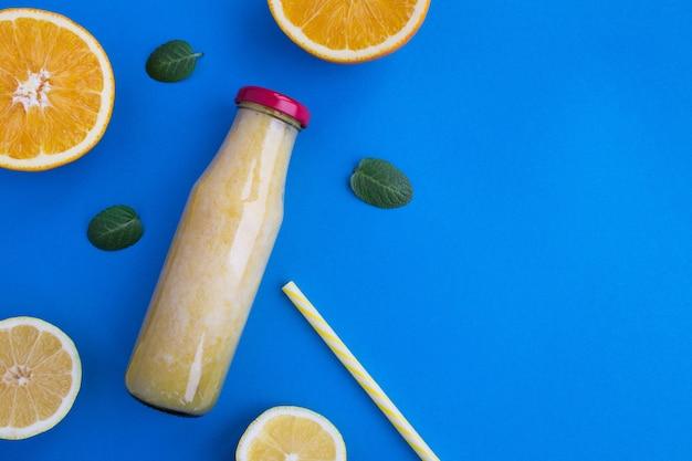 Вид сверху смузи с фруктами в стеклянной бутылке