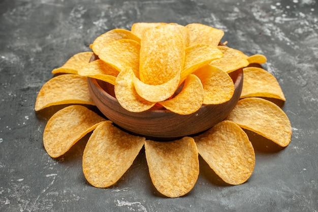 Вид сверху закуски для друзей с вкусными картофельными чипсами на сером фоне
