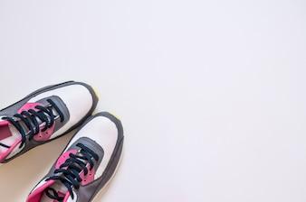 Вид сверху кроссовки на белом фоне. Фитнес-одежда и оборудование. Спортивная мода, Спортивные аксессуары, Спортивная экипировка. Концепция здорового образа жизни, спорта и диеты. Спортивное оборудование.